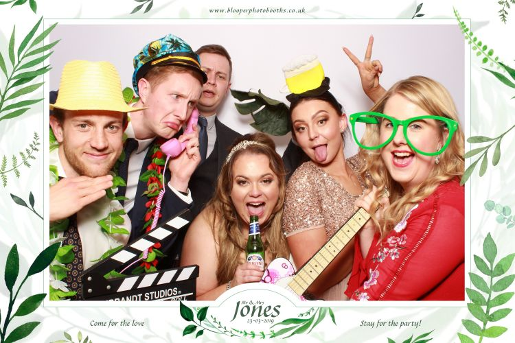 A simple plain white photo booth background at a wedding with green leafy graphics