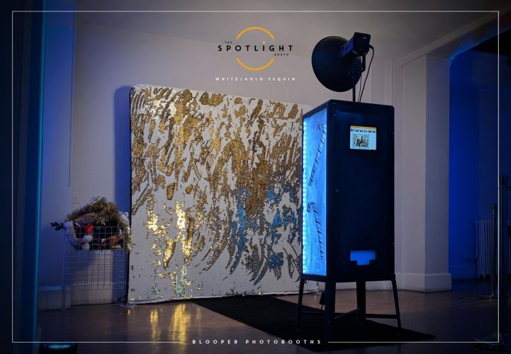 Christmas themed open style photo booth set up with a white and silver sequin backdrop