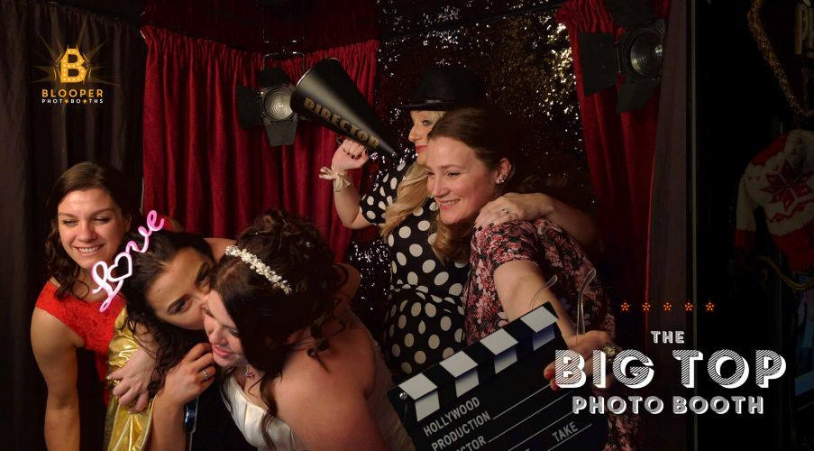 Wedding guests and props inside the Red Carpet themed Big Top photo booth