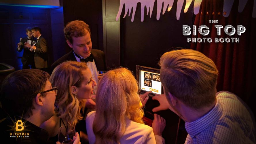 Guests at a Christmas party using the integrated touch screen sharing station on the photo booth