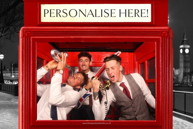 3 wedding guests posing with London themed props in the red phone box photo booth scenery