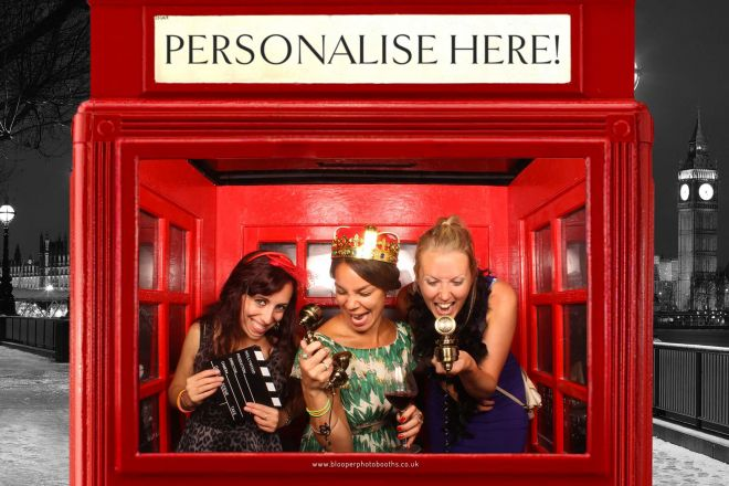 Guests singing into retro phone props in the London themed red phone box photo booth