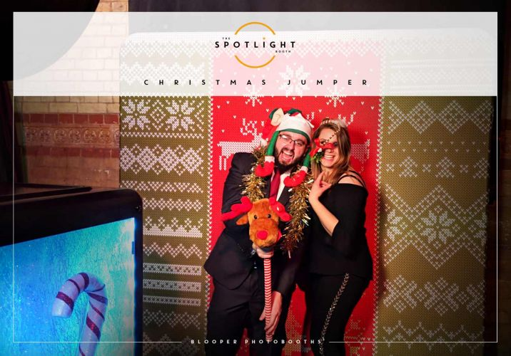 Party guests using the Christmas themed photo booth and 'Christmas Jumper' backdrop