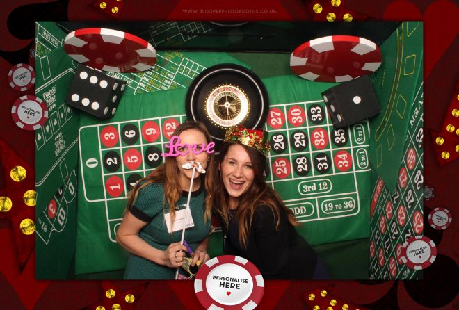 Playing card props alongside a roulette wheel and game tables in the Casino theme photo booth