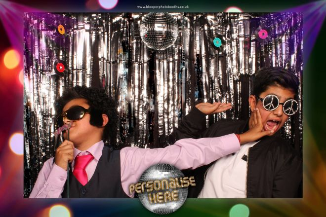 Two boys posing with Disco props around the Disco photo booth scenery