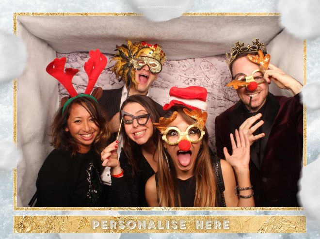 Christmas party guests surrounded by snowy scenery in the photo booth