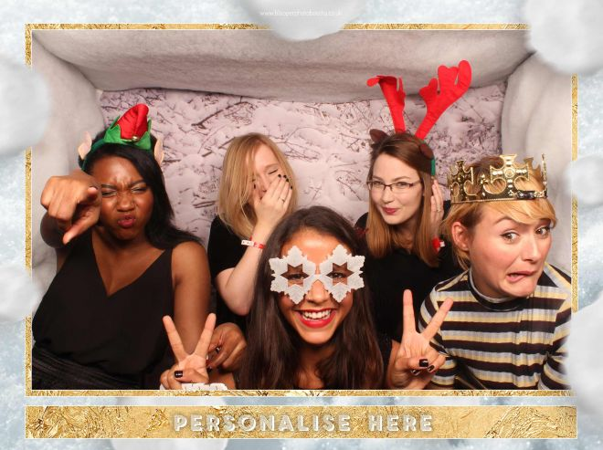 Laughing guests at a Christmas party inside the extra large photo booth with snowy backdrop