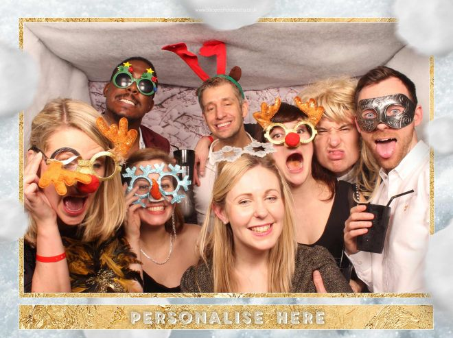 8 people with Christmas themed props inside the snowy Christmas photo booth
