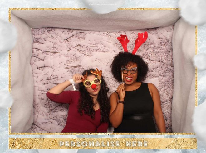 Christmas party guests pose with Christmas props in the snowy photo booth scenery