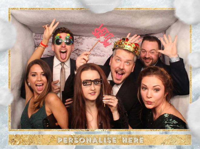 A large group of 6 people in the Christmas party photo booth