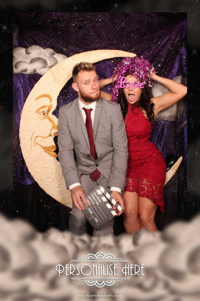 Two wedding guests take a seat on the Paper Moon photo booth seat