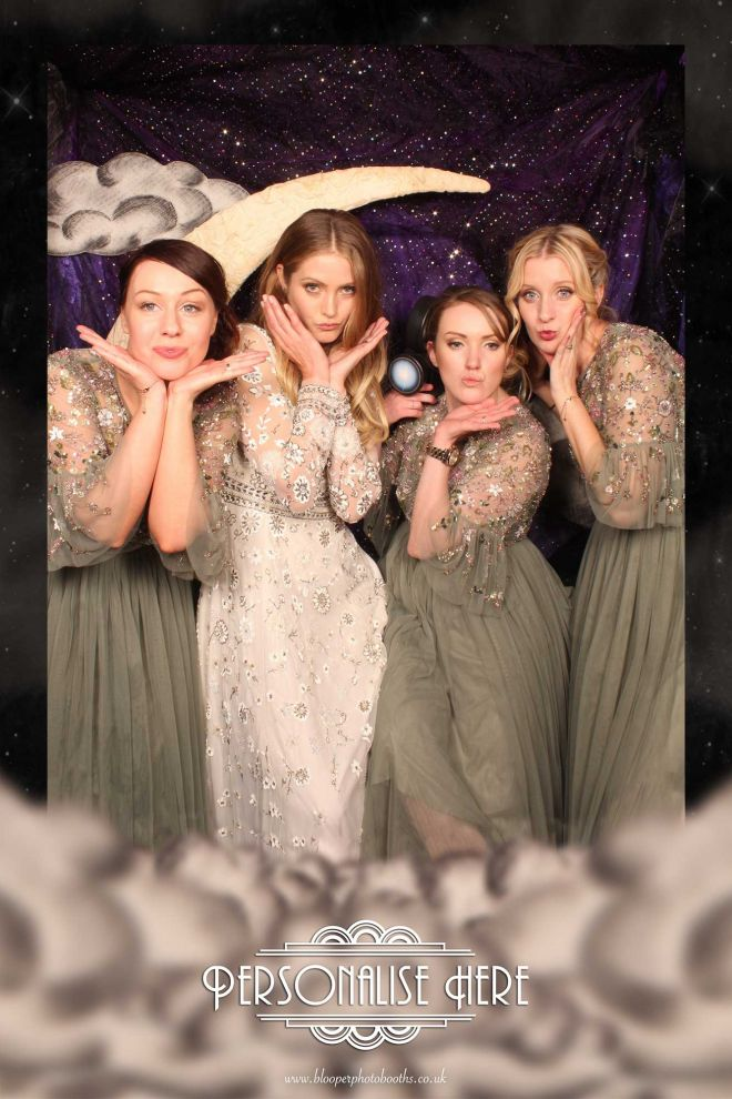 A bride and her bridesmaids pose in the photo booth with the Paper Moon