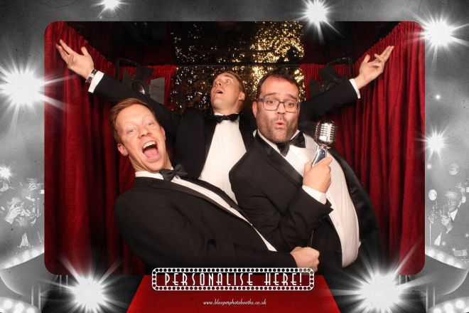 Black tie guests enjoying the VIP Red Carpet themed photo booth background