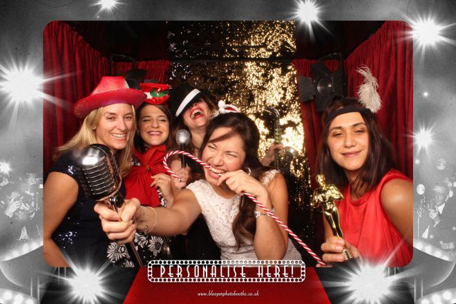 Party guests with Christmas props inside the Red Carpet themed photo booth scenery