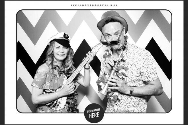 Wedding guests having fun with the props against the Chevron photo booth backdrop