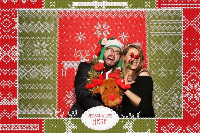 A couple laughing with lots of Christmas props in the Christmas jumper themed photo booth.