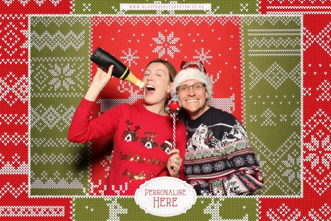 A couple wearing Christmas jumpers in the Christmas jumper themed photo booth