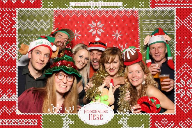 A group of 8 party goers wearing Christmas props in the ugly Christmas jumper themed photo booth