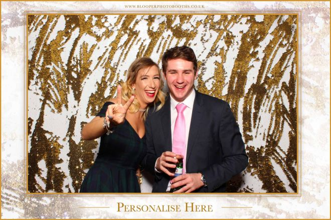 A romantic portrait of a couple against the white and gold mermaid sequin photo booth backdrop