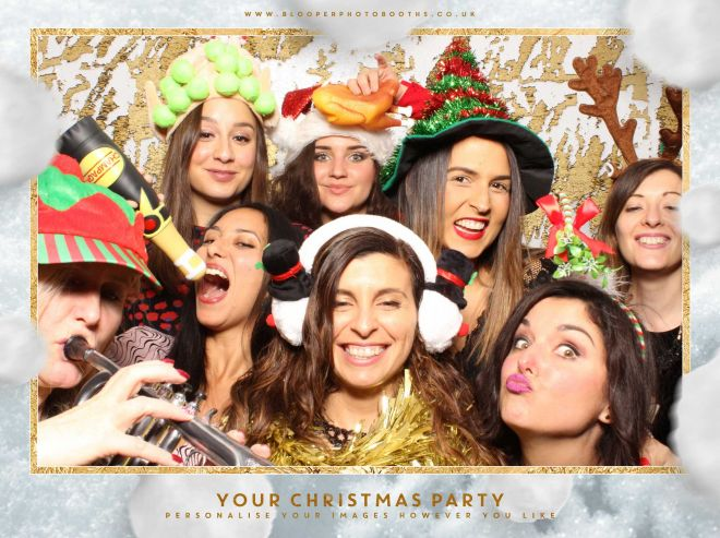 A Christmas party photo booth with a white and gold mermaid sequin backdrop